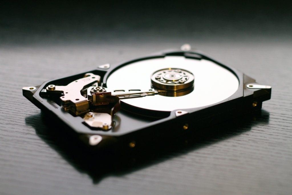Intérieur d'un disque dur traditionnel avec plateau et bras.